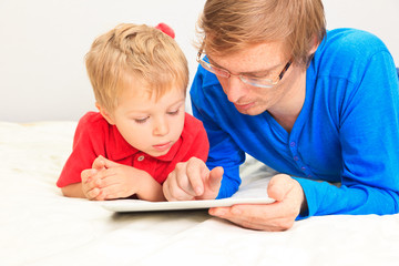 father and son looking at touch pad at home