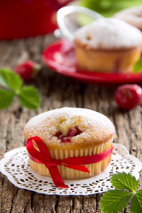 Strawberry muffins on a wooden board.