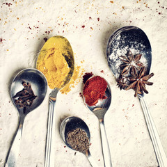 Spoons with spices lying on the flour background