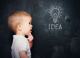 baby child at the blackboard with chalk drawn bulb symbol ideas
