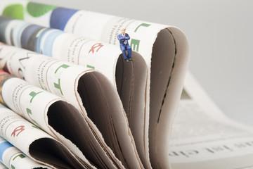 Gesachäftsmann auf Zeitungen sitzend