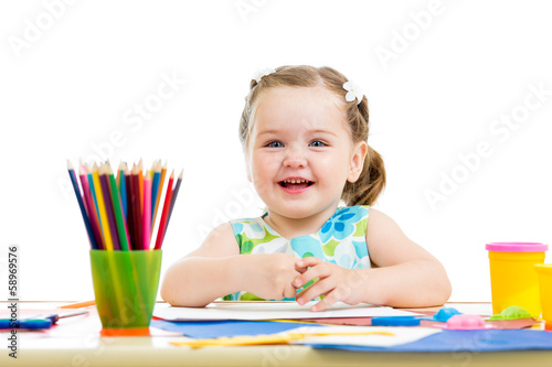 happy kid drawing with pencils