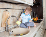 little kid boy washing dish on kitchen