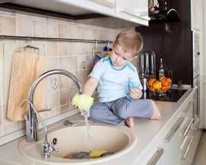 little kid boy washing dish on kitchen