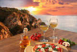 Italian pizza and glasses of wine against Calabria coast, Italy