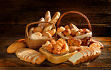 Fotoroleta Variety of bread in wicker basket on old wooden background.
