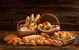 Fototapety Variety of bread in wicker basket on old wooden background.