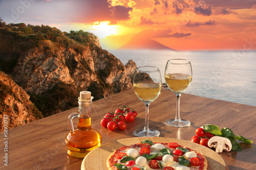 Fotobehang Boord Italian pizza and glasses of wine against Calabria coast, Italy