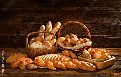 Fototapeta Variety of bread in wicker basket on old wooden background.