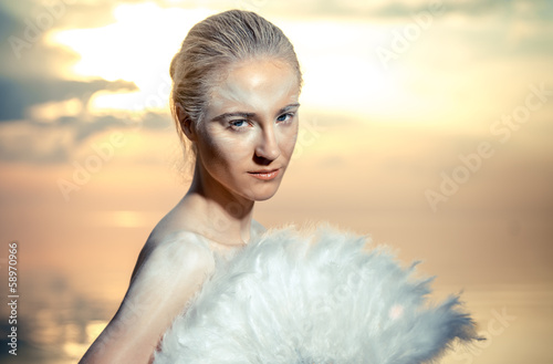 Woman with white feathers fan over sunset sky background