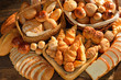 Variety of bread in wicker basket on old wooden background. - 58971315
