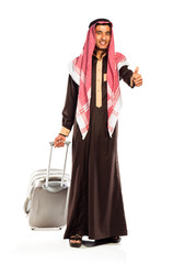 Young smiling arab with a suitcase and thumb up isolated on whit