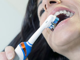 brunette woman brushing teeth with electric toothbrush