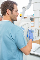 Male Nurse Adjusting Xray Machine