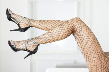 Long and sexy legs in elegant high heels and fishnet stockings