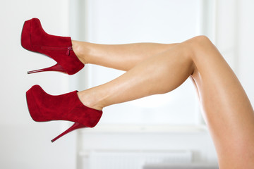 Legs of a woman wearing fishnet stockings and red ankle boots