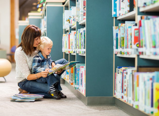Student With Teacher Reading Book In Library