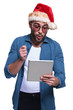 man in santa hat is reading something surprising on pad