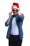 man with santa claus hat talking on phone and pointing