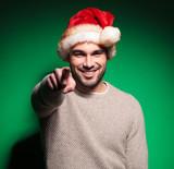 smiling santa man is pointing finger