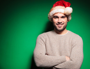 man wearing santa claus hat standing with hands crossed