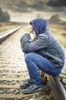 Sorrowful boy on the railway