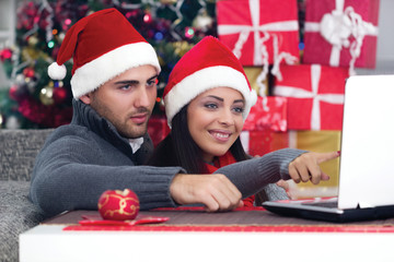 Happy smiling couple using a laptop at home in Christmas