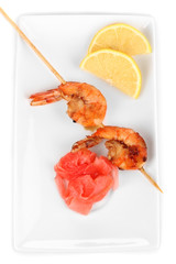 Shrimp skewers on plate with ginger and lemon isolated on white