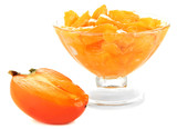 Half persimmon with jam in glass saucer isolated on white
