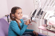 little girl in dental office with dentist tools