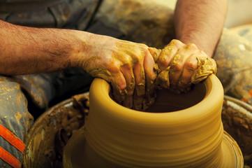 Craftsman making vase on pottery wheel
