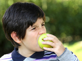 child bite on a apple in the middle of the lawn