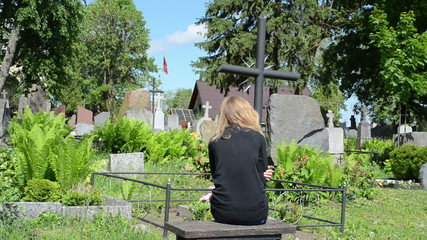 Young girl sit near soldier boyfriend grave. Lithuania flag