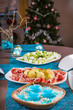 Holiday-decorated table, Christmas tree, ham and melone, and sal