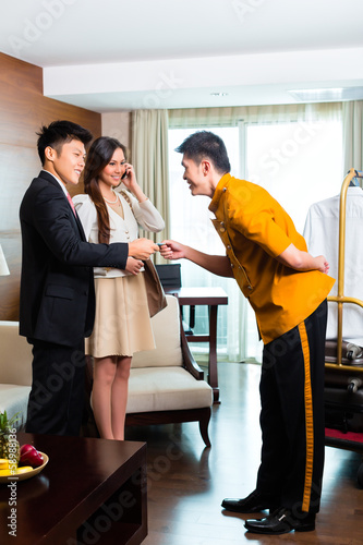 Asian Chinese bell boy or porter receiving tip