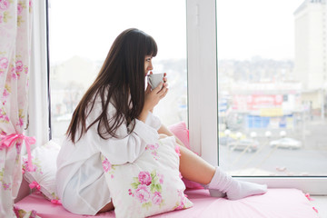 Lovely young woman drinking her morning coffee