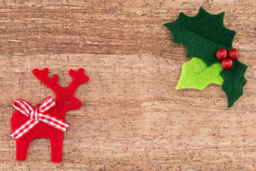 Christmas holly and reindeer isolated a wood background