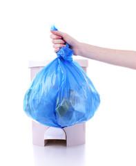 Hand holding trash bag, isolated on white
