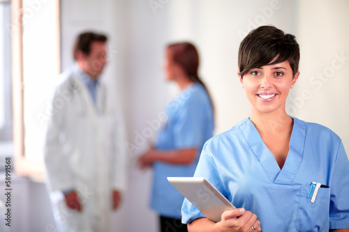 Fototapeta Lovely latin nurse on blue uniform standing