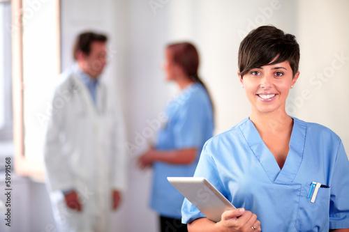 canvas print picture Lovely latin nurse on blue uniform standing
