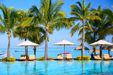 Swimming pool with  umbrellas on beach in Mauritius - 58991764