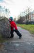 Little boy pushes a large rock
