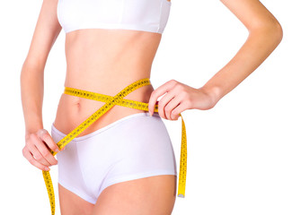 Young fit female measuring waist