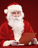 Portrait of happy Santa Claus holding Christmas letter