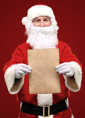 Happy Santa Claus holding Christmas letter