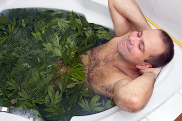 man taking a bath full of marijuana leaves