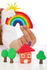 Clean environment concept - child hand with colorful clay figure