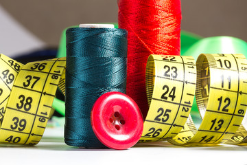Spools of thread, needle, measuring tape, button