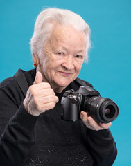 Old woman with photo camera on a blue background