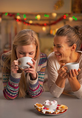 Smiling two girlfriends having christmas snacks in kitchen